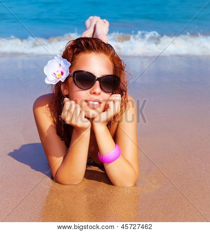 Closeup portrait of beautiful female with fresh orchid flower in red hair lying down on the beach, luxury spa resort, summer traveling and vacation concept