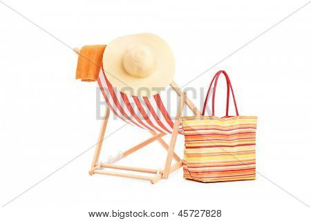 Sun lounger with orange stripes and summer accessories, isolated on white background
