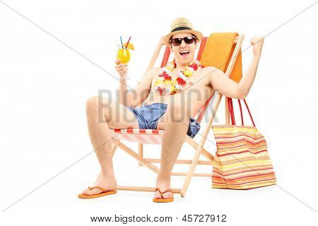 Happy young man enjoying a cocktail and sitting on a beach chair, isolated on white background