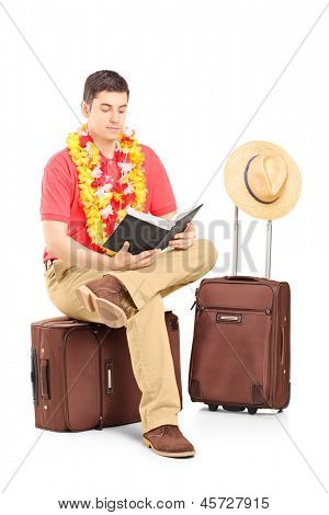 Male tourist sitting on a briefcase and reading a book, isolated on white background