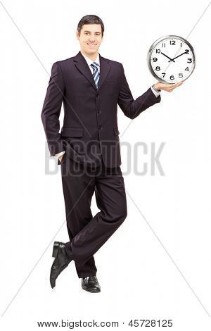 Full length portrait of a young man in suit holding a clock isolated on white background