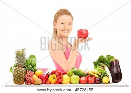 Young smiling female holding a red apple and posing behind a table full of vegatebles and fruits isolated against white background
