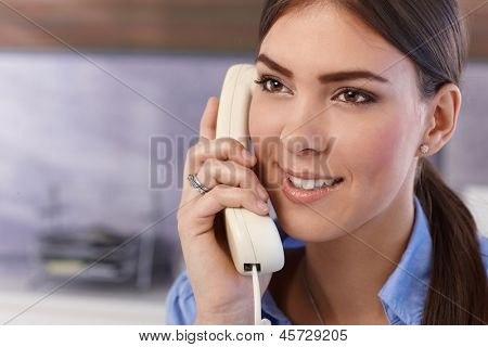 Happy young pretty woman on landline phone call, smiling.