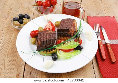 meat savory : beef fillet mignon grilled and garnished with baked apples , tomatoes and juice on wooden table
