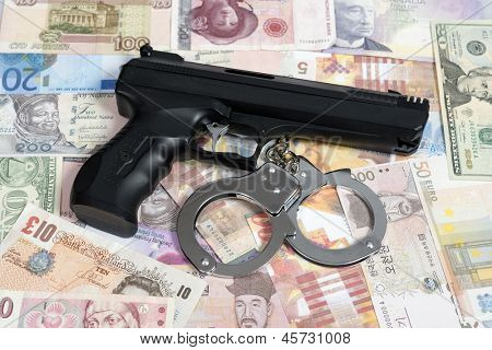 Currency from world with handcuffs and handgun