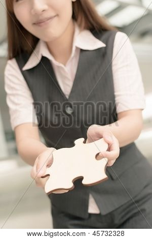 Asian business woman hold a wooden puzzle, closeup portrait in outside of office buildings.
