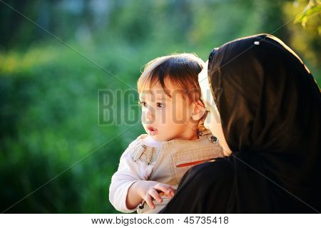 Middle Eastern Muslim mother playing with her little baby in green park and holding him in arms