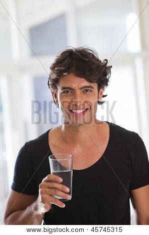 Portrait Of A Happy Young Man Holding A Glass Of Water