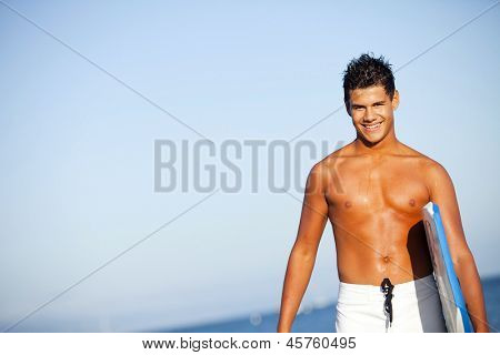 Young man at the beach with a boogie board