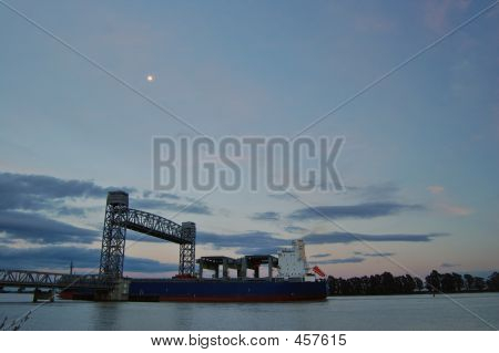 Freighter Passing Under A Drawbridge
