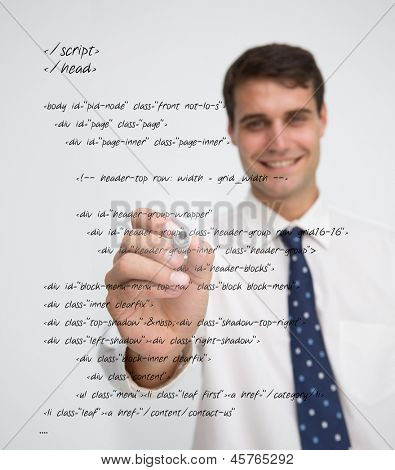 Smiling businessman writing in sql language on a transparent board