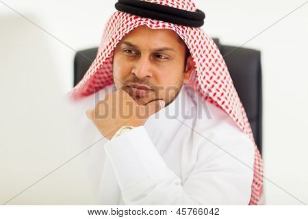 thoughtful arabic businessman looking at computer screen