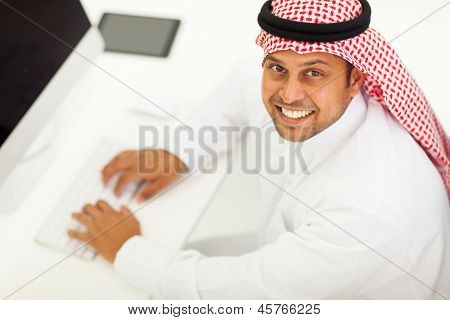overhead view of a cheerful arabic businessman using modern computer