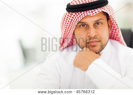 handsome arabic businessman close up portrait in modern office