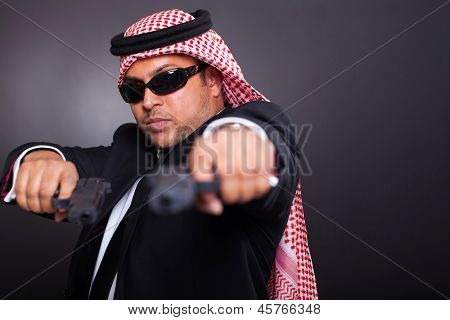 middle eastern bodyguard posing with guns on black background