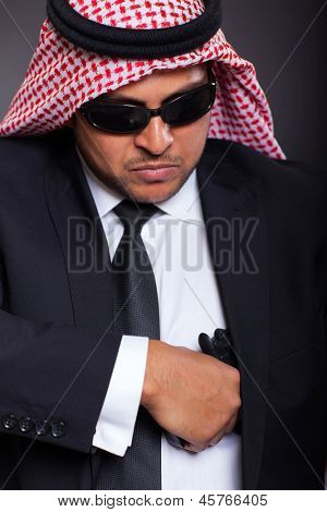 dangerous middle eastern hitman drawing his handgun on black background