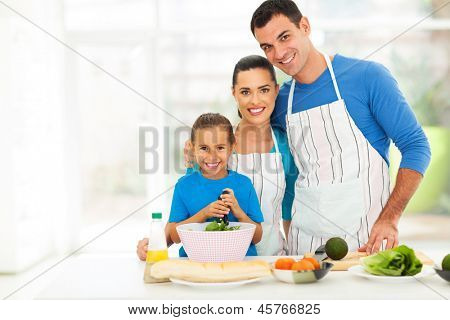 adorable young family cooking in kitchen at home