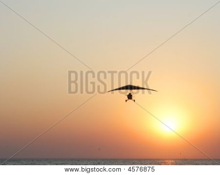 Hangglider In Action Against A Sea Sunset