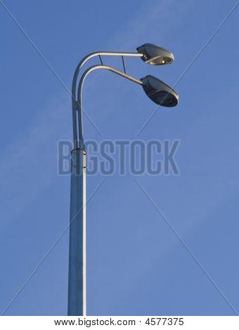 Two Grey Street Lamppost In Blue Sky
