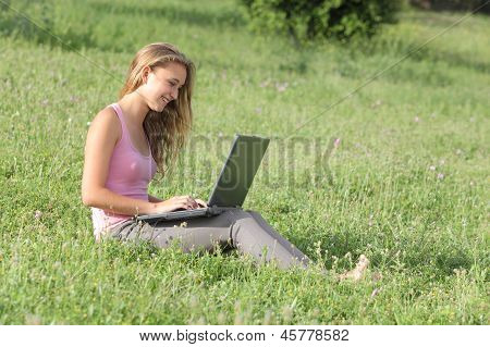 Beautiful Teenager Girl With A Laptop On The Grass