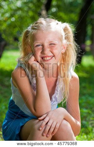 Sweet, Playful Blond Girl Sitting In The Green Garden And Backing Chin In His Hand - Smiles And Wink