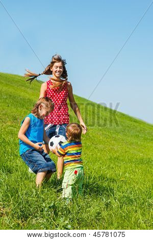 Three laughing kids playing with a ball on green grass