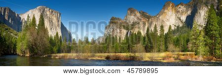 Yosemite Valley panorama showing the upper Yosemite Falls and the Bridalveil Falls with the Merced river in the foreground