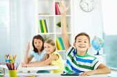 stock photo of diligent  - Portrait of clever schoolboy raising hand at workplace with two classmates behind - JPG
