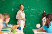 Portrait of smart teacher standing by blackboard and looking at schoolkids while one of pupils writi