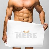 stock photo of stripper  - Naked muscular man covering with a banner   - JPG