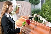 pic of coffin  - Mourning woman on funeral with red rose standing at casket or coffin - JPG