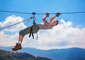 stock photo of harness  - Active happy woman overhanging on tightrope in the mountains on blue sky background - JPG
