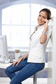 Casual portrait of happy businesswoman using mobile phone, sitting on office desk in jeans.