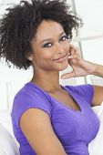 foto of settee  - A beautiful mixed race African American girl or young woman looking happy and thoughtful - JPG