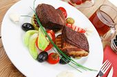 savory food : roast beef garnished with apple juice , green and black olives, red hot peppers on woo