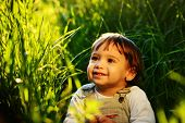 Happy baby boy on the meadow with flowers