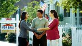 stock photo of real-estate agent  - A young couple purchases a new home from a real estate agent - JPG