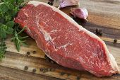 Raw red sirloin steak with fresh herbs, garlic and peppercorns.