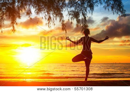 Young yoga woman silhouette, exercises on the beach during a beautiful sunset