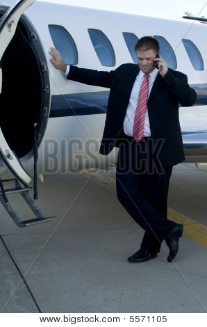 Businessman On Cell Phone In Front Of Corporate Jet