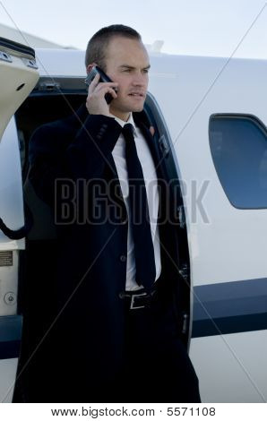Businessman On Cell Phone Exiting Corporate Jet