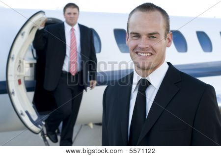 Young Businessmen In Front Of Corporate Jet