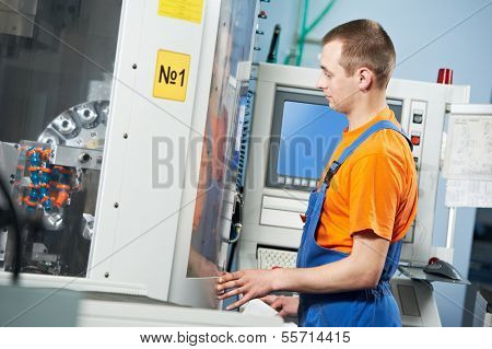 manufacture technician worker near cnc milling machine center at tool workshop