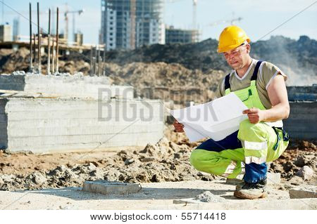 One engineer builder with blueprint plan draft at construction site