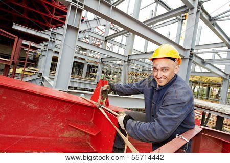 builder worker in uniform at construction site in front of metal construction frames