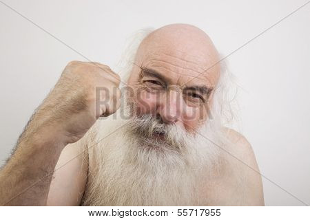 Portrait of shirtless senior man throwing a punch against white background