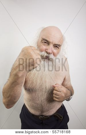 Portrait of shirtless senior man throwing a punch over white background