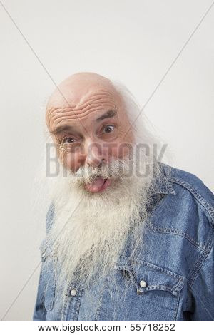 Portrait of senior man sticking out tongue over gray background