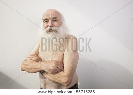 Portrait of shirtless senior man with arms crossed against white background