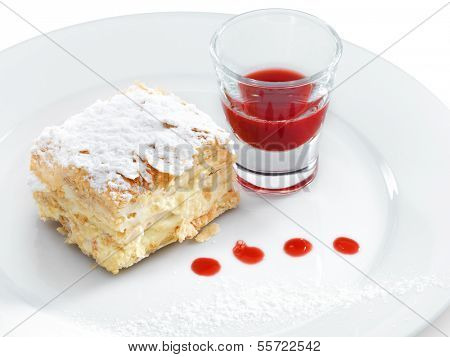 Delicious and yummy Napoleon cake with confectioners sugar and  berry topping on a round plate